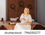 happy pregnant woman in a white ... | Shutterstock . vector #796050277