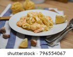 Small photo of Pasta with shrimps and cream souse on the white plate with lemon and garlic