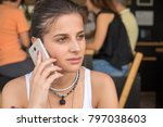 Small photo of Girl talk to the smart phone in a coffee shop. Mild smile on the face. People in the background.