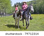 A woman and a young girl on horseback riding in the pasture. - stock photo