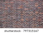 Small photo of English bond brick wall, alternating stretching and heading courses, with the headers centred over the midpoint of the stretchers, and perpends in each alternate course aligned, dark and red bricks.