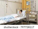Small photo of Sick young woman laying in hospital bed with Central Venous Catheter (CVC) being administered fluids and Parenteral Nutrition (PN)