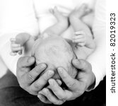 A powerful image of a father's hands hold his newborn child. - stock photo