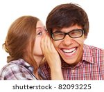 Pretty girl talking secret to young man in his ear, man laughing over isolated white background - stock photo