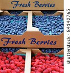 Piles of blueberries and raspberries in cardboard boxes at a farmers market - stock photo