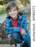 cute happy boy, posing on old farm equipment, blue plaid outfit with hood, necklace and jeans - stock photo