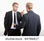 two young businessmen standing, discussing, arguing - isolated on light gray - stock photo