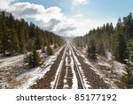 Rail tracks in Canada with snow and trees - stock photo