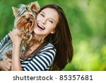 Stock photo woman beautiful young happy with long dark hair in striped sweater holding small dog 85357681
