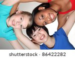 Big smiles in fun team group huddle by mixed race african american, oriental Japanese and blonde caucasian teenage school student girl friends looking down to camera. - stock photo