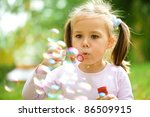 Cute Little Girl Is Blowing A...