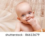 Little baby with a hand in his mouth looking at camera - stock photo