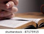 hands of a man praying over a... | Shutterstock . vector #87175915