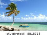 Palm tree and boat at a stunning white sand tropical beach, Punta Cana, Dominican Republic - stock photo