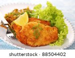 Wiener Schnitzel on white plate with salad and lemon. - stock photo