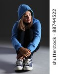 Hoodie on for distressed and frightened young blonde teenager girl sitting on floor looking scared and alone with big sad eyes, wearing jeans and blue jumper. - stock photo