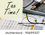Tax forms with pen, calculator, glass and sticker. - stock photo