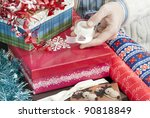 Small photo of Close-up of a man's hand holding tape surrounded by christmas gift wrapping accoutrement.