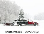 A snow covered truck sits in a field during the Christmas holiday season - stock photo