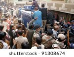 Small photo of HYDERABAD, PAKISTAN - DEC 22: People surround police armored personal carrier (APC) while policemen carry arrested dacoit at Liaquat Colony in Hyderabad on Thursday, December 22, 2011.