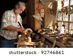 Wood worker carving wood in a derelict shed - stock photo