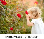 Beautiful Child Smelling Rose...