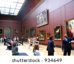 Large  painting gallery at the Louvre museum in Paris, people looking and museum guards. - stock photo