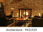beautiful sitting area with leather couches by fire - stock photo