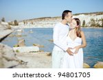 the happy couple walking embraced along the shore of Lake - stock photo