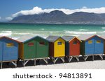 Beach huts with mountain backdrop and ocean - stock photo