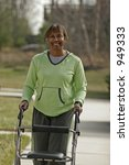 middle-aged woman using walker outside for exercise - stock photo