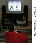 teen youth playing video game in front of television using game controller - stock photo