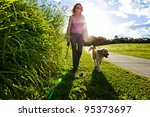 Stock photo young woman and golden retriever walking in the grass 95373697