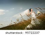 Bride in a field with flowers - stock photo