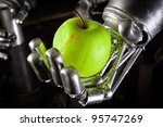 A robot hand holding a fresh apple closeup - stock photo