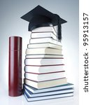 Black graduation cap on pile of books with diploma tube - stock photo