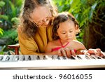 asian ethnic old female teaching child play piano - stock photo
