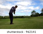 A junior golf champion lifts a shot onto the green - stock photo
