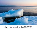Ice melting on the beach in the sunset - stock photo