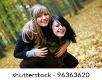 two young friendly women in autumn - stock photo