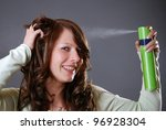 young woman styles her hair with hair spray - stock photo