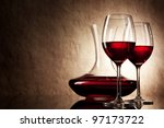 decanter with red wine and glass on a old stone background - stock photo