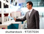 handsome businessman handing over air ticket at airline check in counter - stock photo