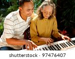 asian ethnic elderly woman play piano together with young adult male - stock photo