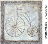 A path for bicycles is marked in concrete with the image of an old style penny-farthing bike - stock photo
