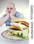 unhappy looking man stares at a big cheeseburger - stock photo