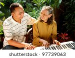 asian ethnic family portrait of elderly mother play piano together with young adult son - stock photo