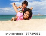 Asian ethnic mother and child happy playing together at tropical beach - stock photo