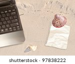 laptop with note on beach working - stock photo