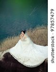 Bride beside lake - stock photo
